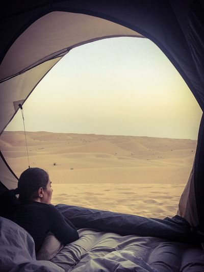 Early morning facing the ocean of dunes. Dubai desert, United Arab Emirates One Person Real People Day Young Adult Sky Nature Outdoors People Camping Leisure Activity Dubai Middle East Desert Nature Beauty In Nature Woman Women Tent Isolated Alone Sleeping Morning Dunes Travel Cold