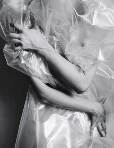 Midsection of woman wrapped in plastic