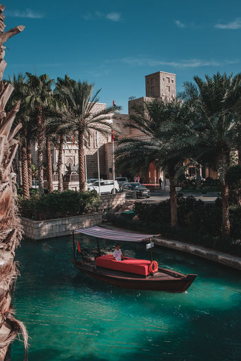 Boats in swimming pool by buildings against sky