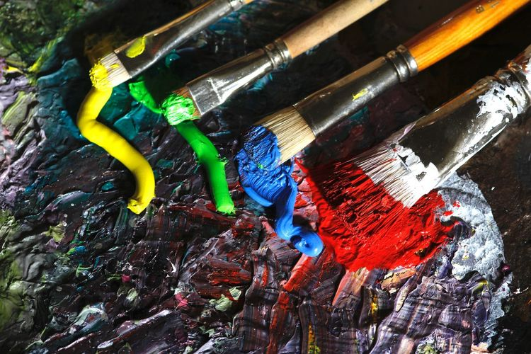 High Angle View Of Paintbrushes On Messy Palette
