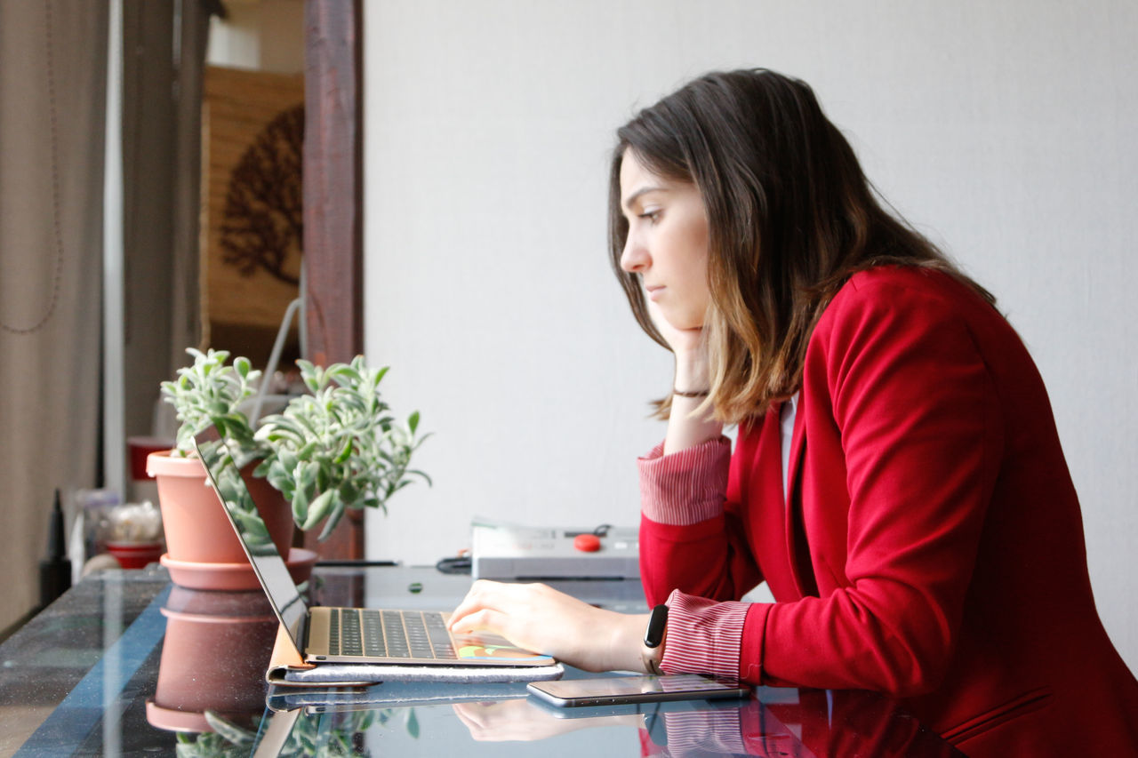 table, sitting, one person, wireless technology, indoors, laptop, technology, casual clothing, using laptop, young adult, plant, real people, young women, day, occupation, women, working, flower, adult, people, adults only