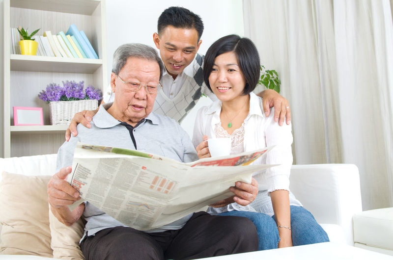 Happy family reading newspaper while sitting on sofa at home