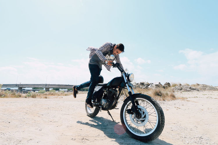 Young man riding bicycle on motorcycle against sky