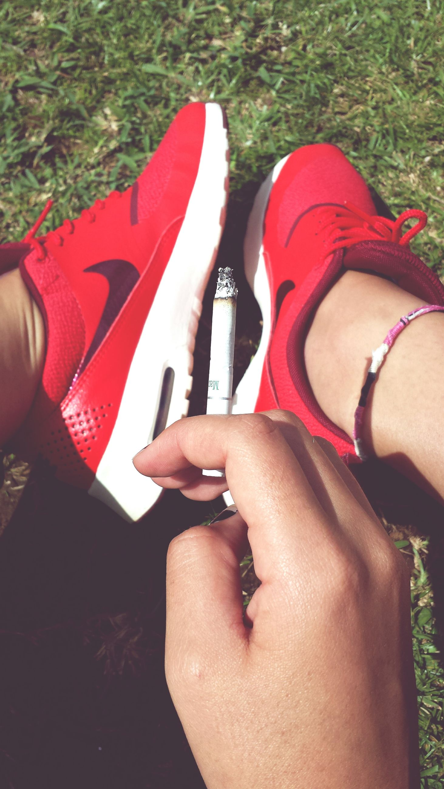 lifestyles, leisure activity, part of, person, personal perspective, low section, sitting, men, relaxation, lying down, red, cropped, resting, shoe, outdoors