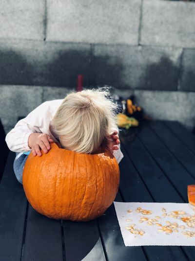 Cute girl with pumpkin sitting on floor