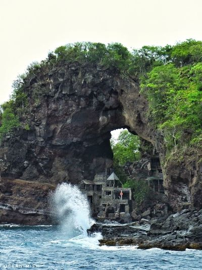 The Moonhole House. In the 1950s, Tom and Gladdie Johnston quit their jobs in the US and came to Bequia an island in the Saint Vincent and the Grenadines. The family that then owned the western tip of the island invited the Johnston's for a picnic and check out a massive rock arch known as the Moonhole. Tom instantly started dreaming of having a campsite below the arch to enjoy picnics. This dream slowly grew up to become a full blown functional house for the Johnston's to live in. Back then, the only road to reach the house was a rocky path along the sea. In his quest to not disturb nature in any way, Tom hand built his house with rocks, driftwood, shells and whalebones. No trees were cut in the making of his house, the tall trees that were in the property still exist and the building has gone on around these tree with them propping out of the living rooms, bedrooms and deck. Upon seeing and visiting the Johnston's new home in the Moonhole, many of his friends requested Tom to build house for them. Tom agreed and aimed to develop the Moonhole property as a 'People Preserve'. He decided to also build a gallery where all the residents could gather for meals on Sunday! Sustainableliving Travelust Wanderlust Spreadthelust Mytravelgram Livebythesea Lifebythesea Saltedlifestyle Rockarch Moonhole Caribbean Bequia Vitaminsea Aquaholic Architecture Nature Natureincorporated Lifestyle Oceantribe Oceanminded Oceanlust Inspired Awesomelocations Tree Water Power In Nature Bridge - Man Made Structure Rock - Object Sky Natural Arch