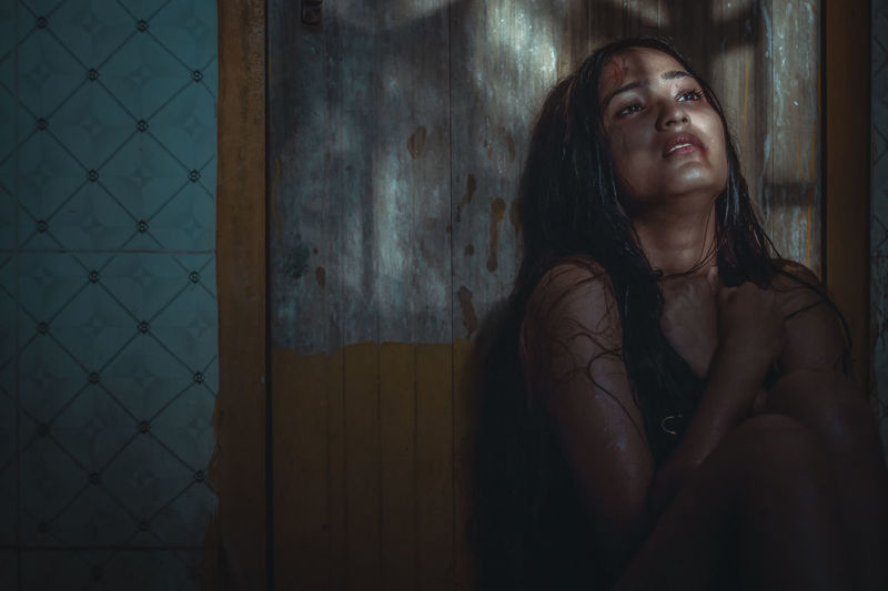 Naked Injured Woman Sitting By Wooden Door