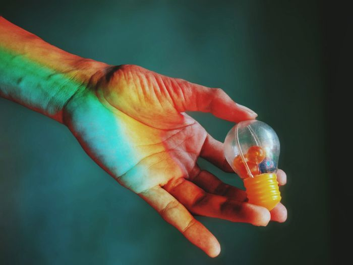 Close-up of hand holding plastic light bulb