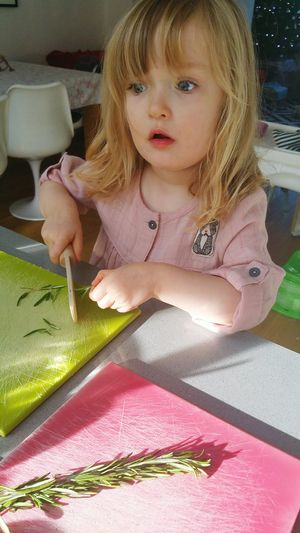 Cute girl playing with rosemary twig on table at home