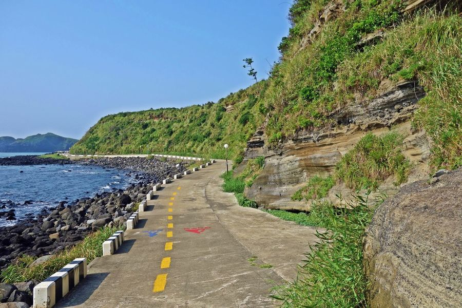 a Eongal coastal walking trail view between a sea and ourcrops of volcanic deposits,jeju island,korea,asia ASIA Basaltic Beautiful Cliff Coast Deposits Grasses Green Island Jeju Korea Mountain Nature Outcrops Rocks Sea Sky Trail Tranquility Travel Trip View Walking Water Waves