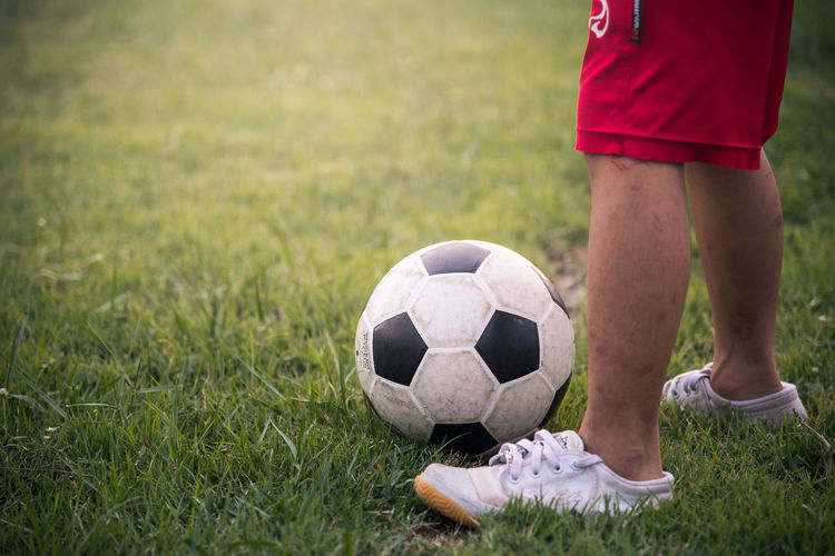 Low section of child playing soccer on field