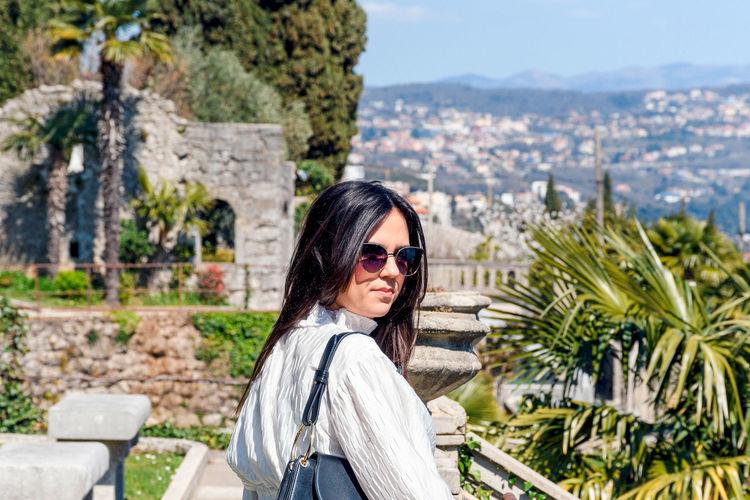 Portrait of beautiful  woman in mediterranean gardens. american gardens park in opatija, croatia.