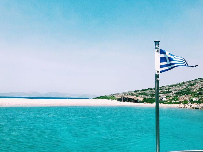 Greek flag in sea against sky
