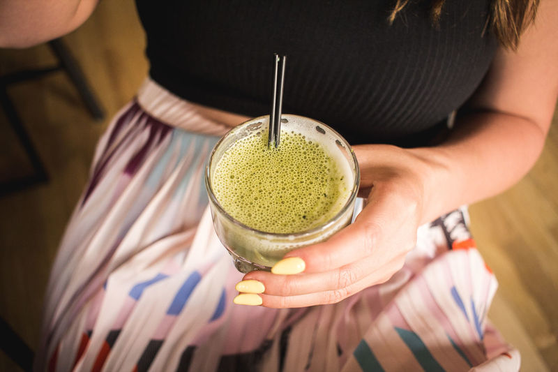 Midsection of woman holding matcha tea