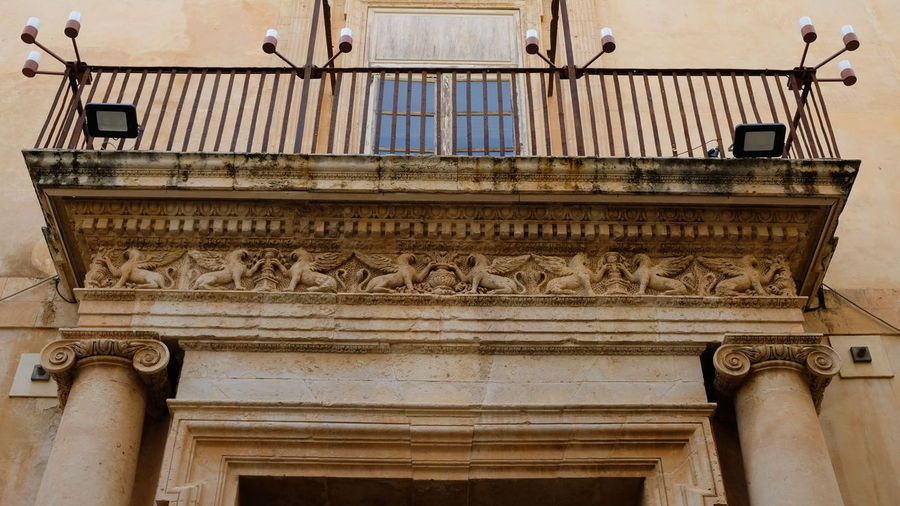 City of Noto. Province of Syracuse, Sicily. This is the entrance of Palazzo Nicolaci. At the top of it, a spectacular winged lions frieze. The entire city of Noto is known as one of the most remarcable examples of the sicilian baroque style. Noto,sicily Syracuse  Sicilian Baroque Architecture Italy Antiques Details Close-up Elaborate Architectural Detail Balcony Rare Peculiar Architecture Palazzo Nicolaci Sandstone Lion Winged Frieze Frieze Detail Column Entrance Gate Portal Building Exterior Architectural Column Travel Destinations