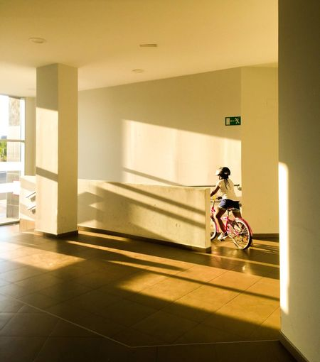 Young woman riding bicycle in building