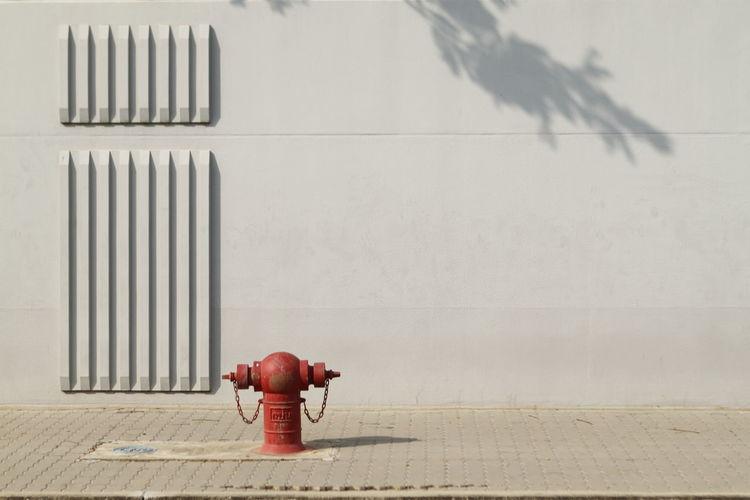 Fire hydrant on sidewalk against wall