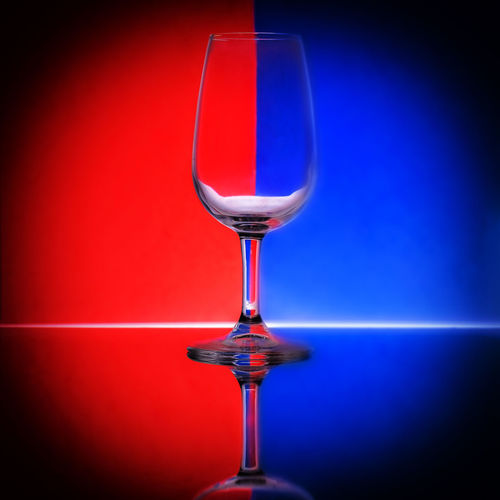 Close-up of wineglass against blue background