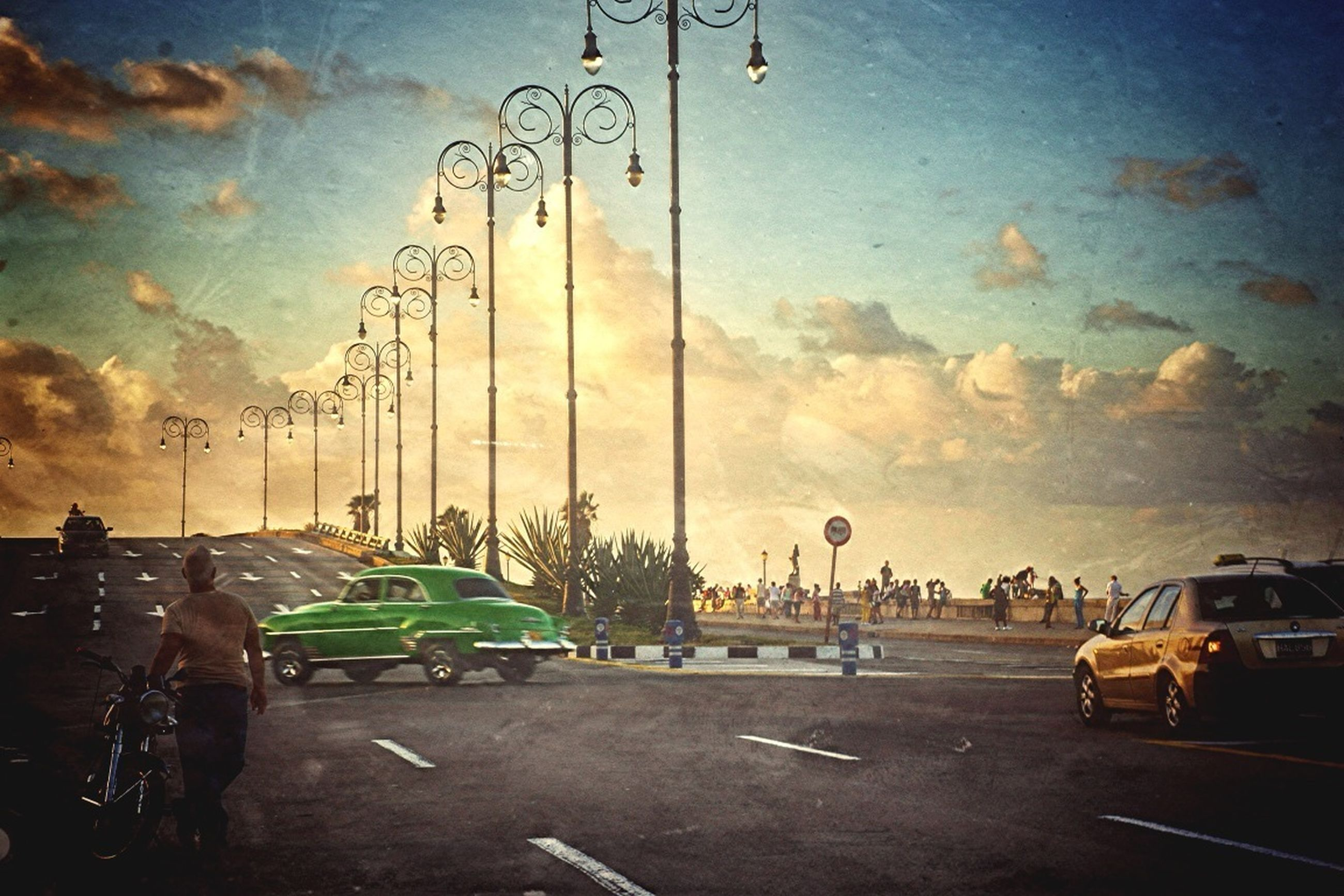 transportation, mode of transport, land vehicle, car, sky, bicycle, street, stationary, road, travel, cloud - sky, parked, parking, men, sunset, parking lot, on the move, outdoors, street light