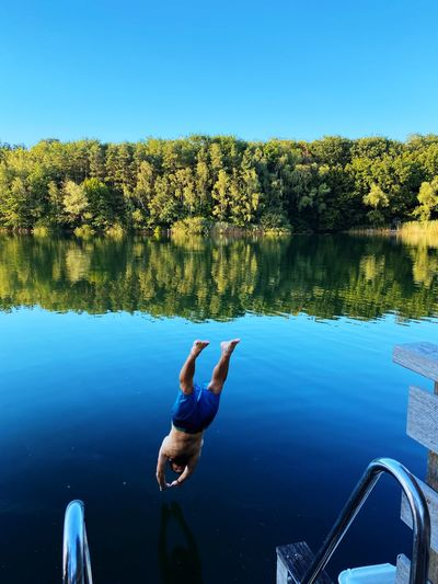 High angle view of man dives into lake against sky