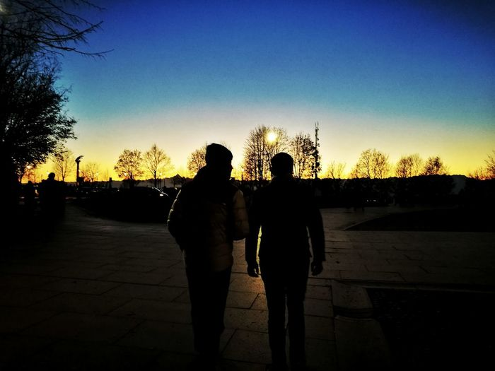 Two People Only Men Silhouette Adults Only Sunset Togetherness Sky People Outdoors Standing Adult Men Blue Down Friends Talking Dark Darkness And Light Friendship Tree Real People Sun