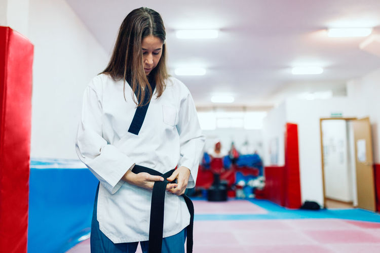 Young woman wearing belt during taekwondo practice