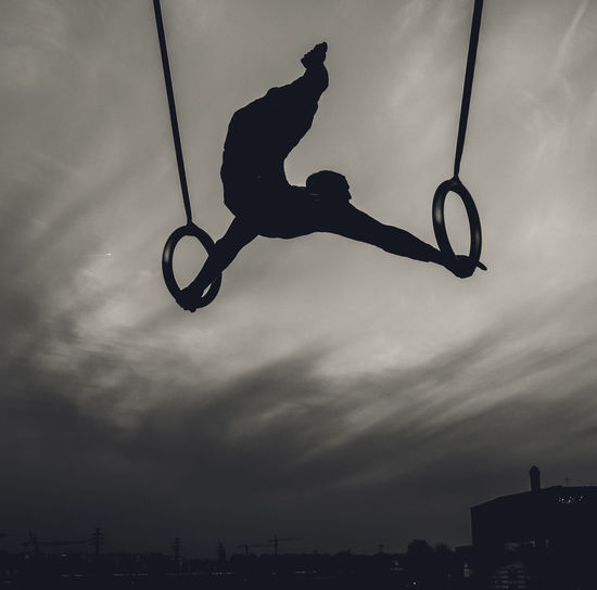 Low Angle View Of Silhouette Man Performing Gymnastics Against Sky