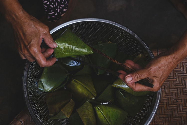 Cropped image of man holding food wrapped in banana leaf