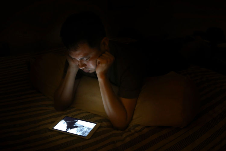 High Angle View Of Young Man Using Digital Tablet On Bed In Darkroom