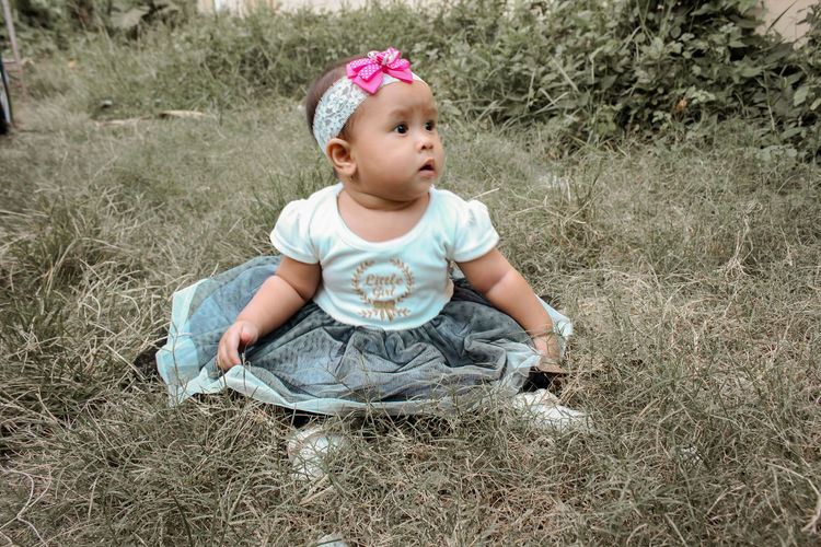 Child Young Baby One Person Front View Real People Childhood Babyhood Innocence Land Plant Cute Casual Clothing Day Nature Sitting Baby Clothing Outdoors Grass