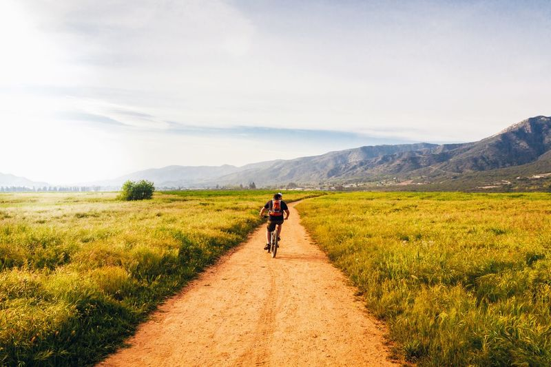 Rear View Of Person Riding Bicycle On Dirt Road On Grassy Field Against Sky