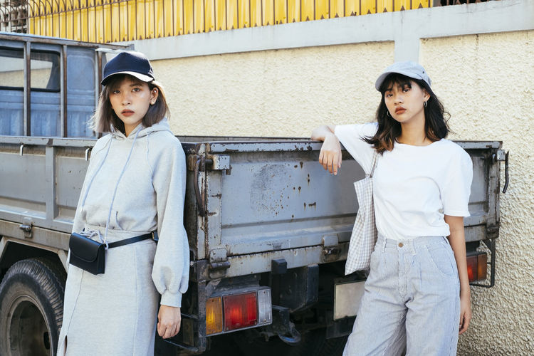 Portrait of friends standing by truck against wall in city