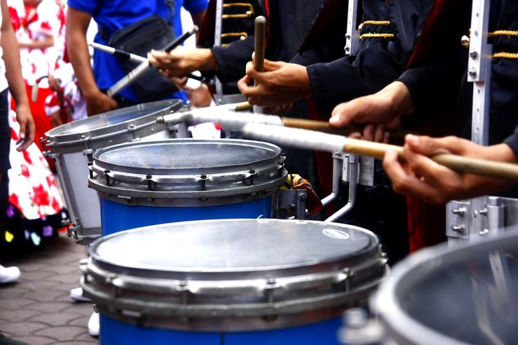 Midsection of musicians playing drums at music concert