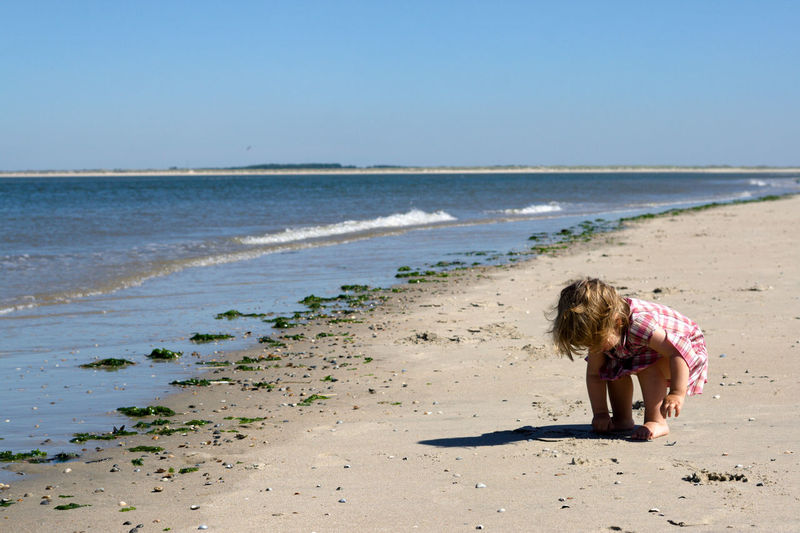 Beach Sea Land Sand Water One Person Sky Child Nature Day Childhood Girls Leisure Activity Sunlight Clear Sky Horizon Over Water Outdoors Hair Horizon Collecting Shells Northsea Eastfrisia Dress Clothing