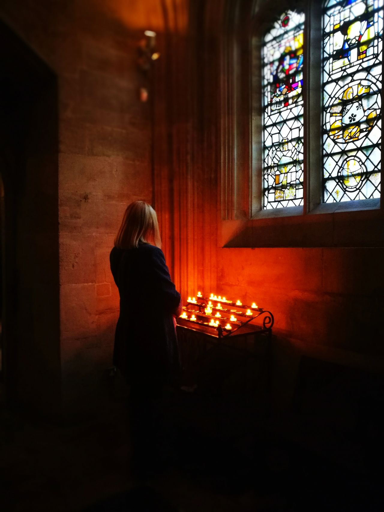 Woman sitting by illuminated candles and window in church