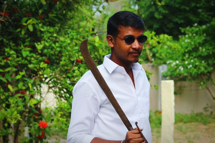 Young man wearing sunglasses holding knife against plants