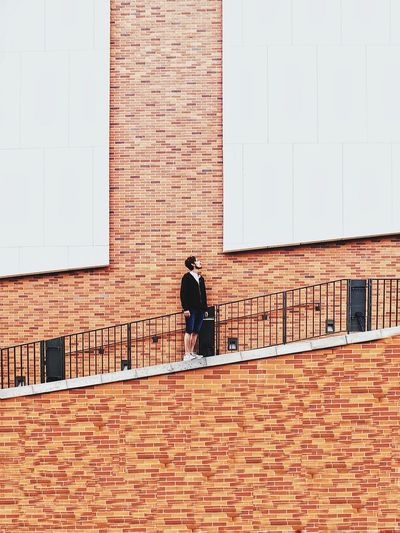 Low angle view of man standing on steps against brick wall