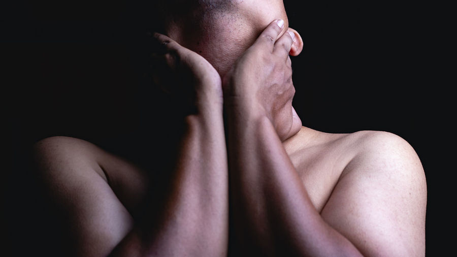 Midsection of shirtless man against black background