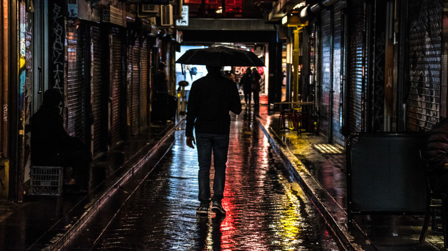 Rear view of man walking on wet road in city at night