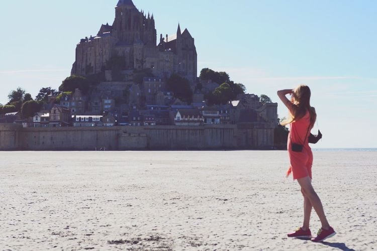 Full length of woman standing at beach with historic buildings in background during sunny day