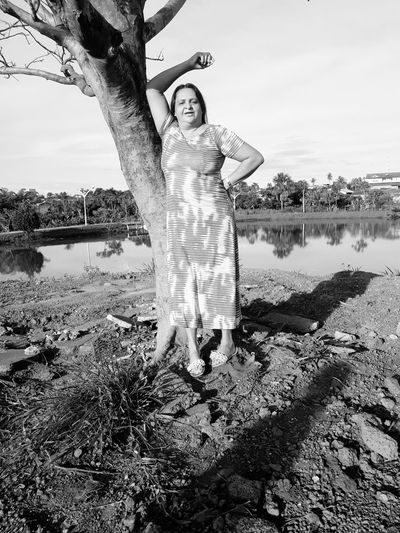Portrait of woman standing at lakeshore