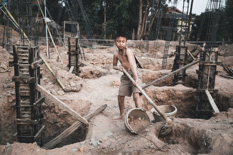 Portrait of a young man standing at construction site