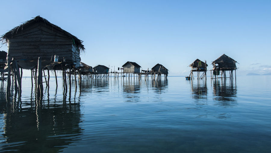 Stilt houses by sea against clear sky