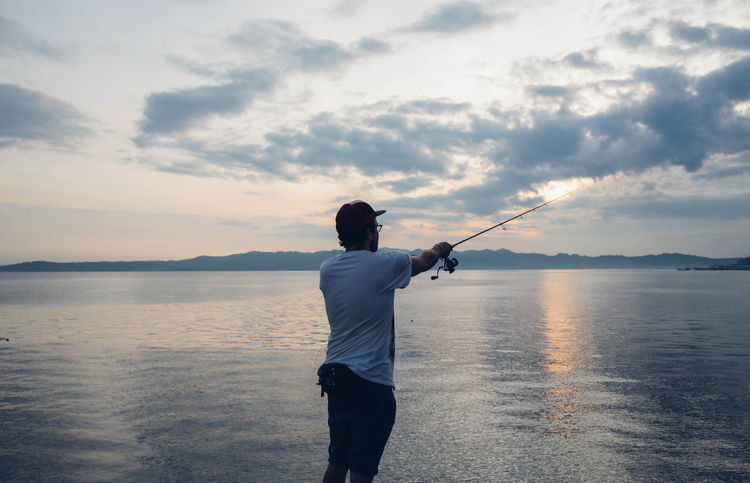 Angler Beauty In Nature Fisherman Fishing Fishing Rod INDONESIA Leisure Activity Light Maluku  Men Morning Nature Ocean Outdoors Rear View Scenics Sea Sea And Sky Sky Standing Sunrise Tranquil Scene Tranquility Tulehu Water
