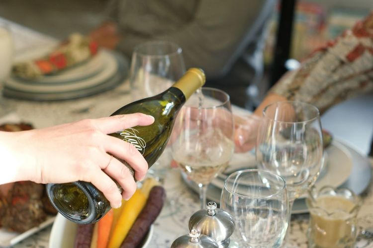 Cropped hand pouring wine from bottle in glass on dining table