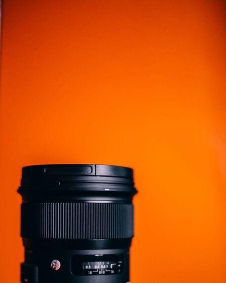 Close-up of camera lens against orange wall