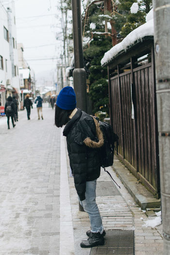Woman standing on sidewalk in city
