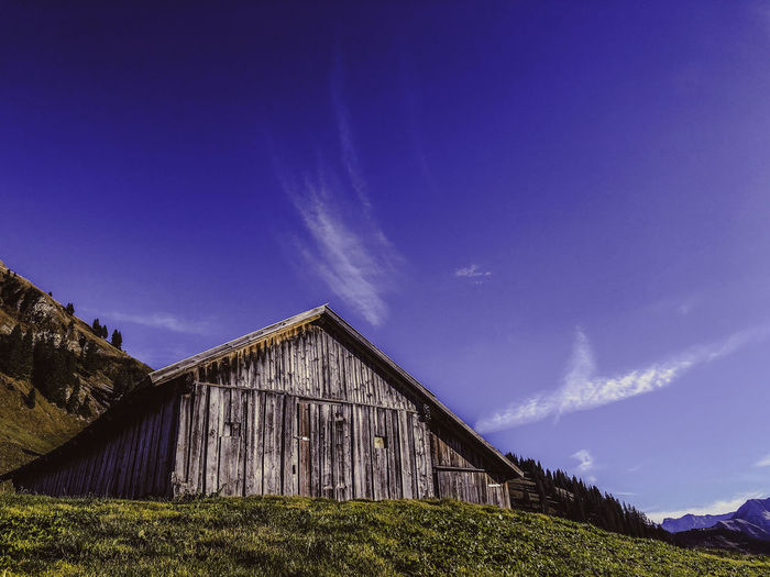 Panoramic view of barn on field against blue sky