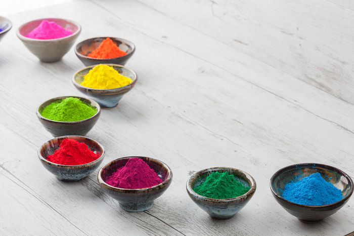 Bright and colorful dyed powder in ceramic cups on white rustic wooden table. Holi Festival Holi Festival Of Colours Close-up Colorful Day Dye Freshness Healthy Eating High Angle View Holi Holi Powder Indoors  Multi Colored No People Powder Paint Talcum Powder Top View Variation