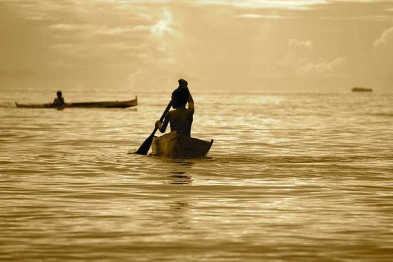 Silhouette men on boat in sea against sky